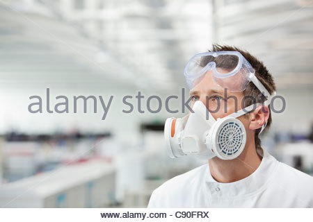 Scientist wearing gas mask in lab - Stock Photo