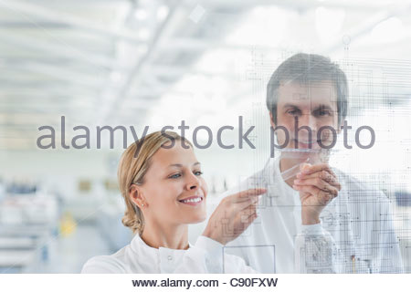 Scientists using touch screen in lab - Stock Photo