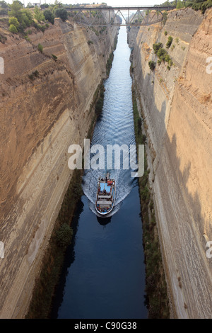 Tourist boat on the Corinth Canal which connects the Gulf of Corinth with the Saronic Gulf in the Aegean Sea - Stock Photo
