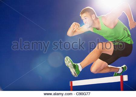Athlete jumping hurdles - Stock Photo