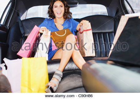 Woman with shopping bags in backseat of limo - Stock Photo