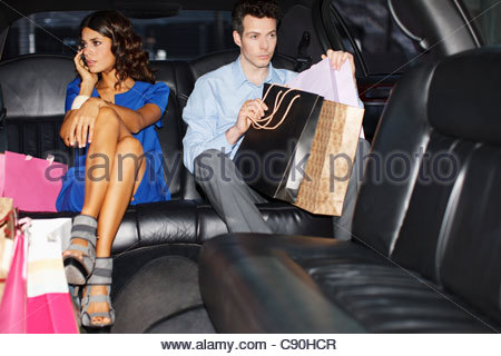 Couple with shopping bags in backseat of limo - Stock Photo