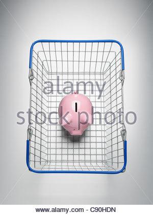 Piggy bank in shopping basket - Stock Photo
