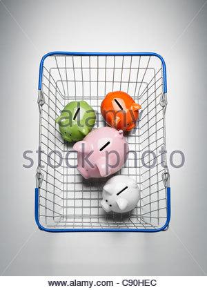 Piggy banks in shopping basket - Stock Photo