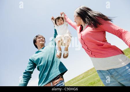 Parents lifting son mid air - Stock Photo