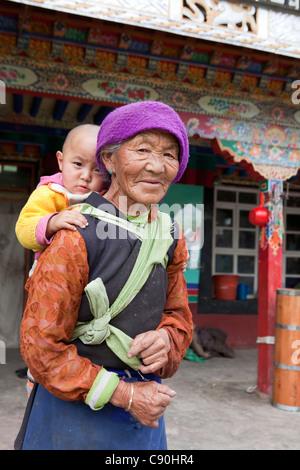 Old Tibetean farmer women with baby in Lhasa, Tibet Autonomous Region, People's Republic of China - Stock Photo