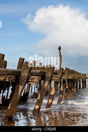 A twisted groyne on Walcott beach at low tide on the north Norfolk coast - Stock Photo