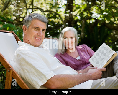 Couple sitting on deckchairs in garden - Stock Photo