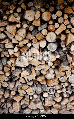 A pile of logs stored ready for use as domestic fuel in a wood burning stove at a home in Shropshire, UK - Stock Photo