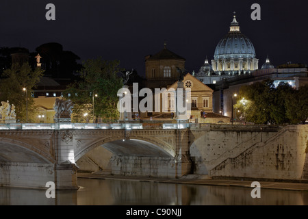 Ponte Vittorio Emanuele II with the dome of St Peters Basilica in the background at night, Roma, Latium, Italy - Stock Photo