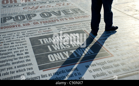 A man standing on the Comedy Carpet on Blackpool Promenade - Stock Photo