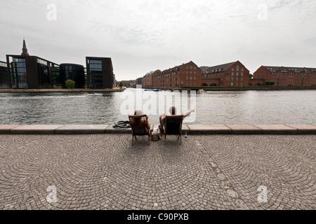 Couple relaxing on the banks of the Havnebadet canal, Copenhagen, Denmark - Stock Photo