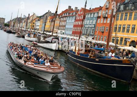 Tourists on a canal cruise, Nyhavn, Copenhagen, Denmark - Stock Photo