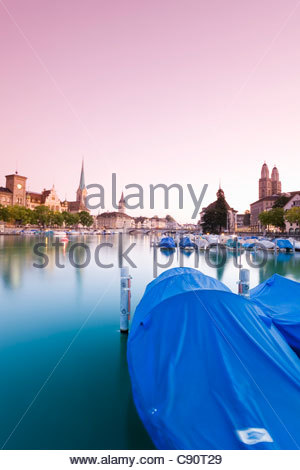 View of the river Limmat and the Fraumunster and St. Peter church right the Grossmunster church in the afterglow - Stock Photo