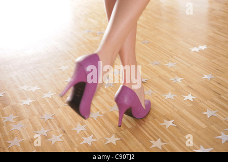 Feet and shoes of a female dancer on a wooden floor - Stock Photo