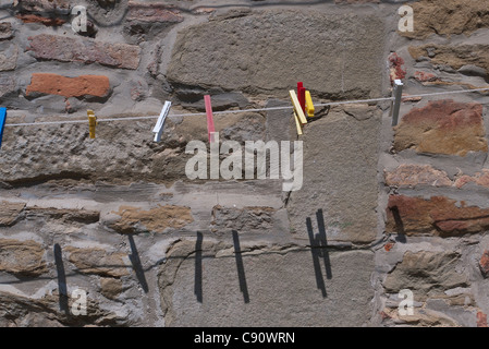 Brightly colored clothes pins hang from a clothes line against a stone wall background in the Italian town of Panicale. - Stock Photo