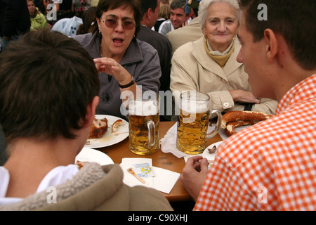Family enjoys beer and meals in the Hofbrau Festzelt at the Oktoberfest Beer Festival in Munich, Germany. - Stock Photo