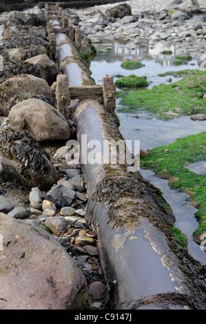 sewage water pipe traversing criccieth beach gwynedd north wales - Stock Photo