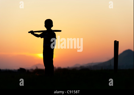 Silhouette of young Indian boy playing cricket against a sunset background - Stock Photo