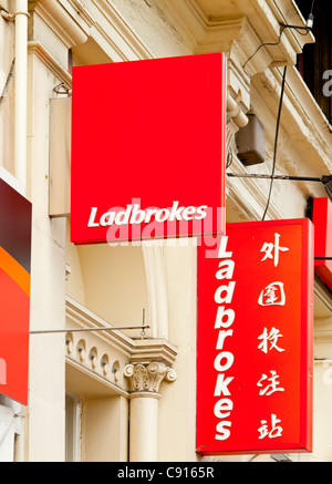 Sign outside a branch of Ladbrokes betting shop with Chinese text in the Chinatown area of central Manchester England - Stock Photo