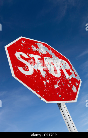 A stop sign on a highway in the American west that is riddled with bullet holes from people shooting it and using - Stock Photo