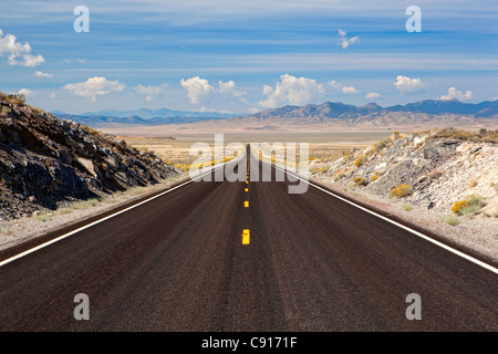 A long straight road going thought the desert to some mountains in Nevada USA - Stock Photo