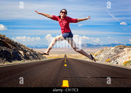 A woman leaping and having fun over a long straight road in the the desert while on holiday in the USA. - Stock Photo
