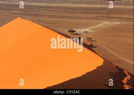 People walking on red sand dune in Sossusvlei, dune 45, Sossusvlei, Namib Naukluft National Park, Namib desert, - Stock Photo