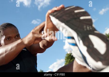 Close up of athlete stretching outdoors - Stock Photo