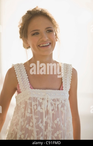 Smiling teenage girl wearing sheer dress - Stock Photo