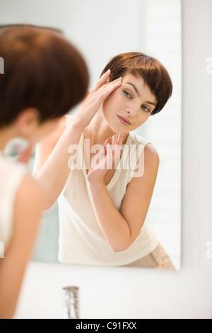 Woman admiring herself in mirror - Stock Photo