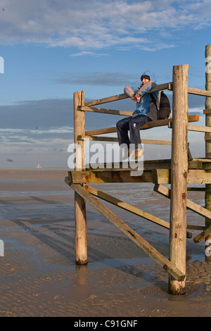 Person on an observation platform at low tide, St Peter-Ording, North Sea, Schleswig-Holstein, northern Germany - Stock Photo