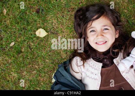 Girl laying in grass outdoors - Stock Photo