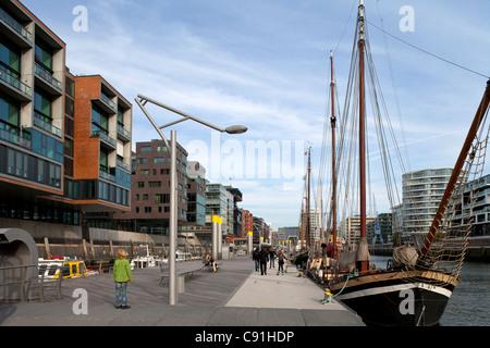 View towards people and sailing ships at Sandtorkai (le.) Kaiserkai (ri.) Sandtorhafen harbour city Hanseatic city - Stock Photo