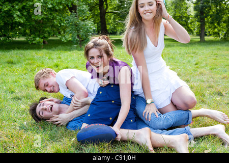 Teenagers playing in grass in park - Stock Photo