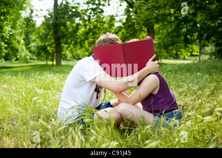 Teenagers hiding behind book in park - Stock Photo