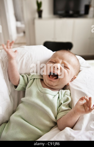Infant crying in bed - Stock Photo