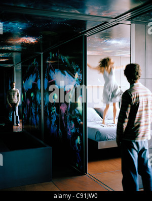 Reflection of woman jumping on the bed Suite on the 13th Floor Designed by Jean Nouvel Hotel Silken Puerta America - Stock Photo