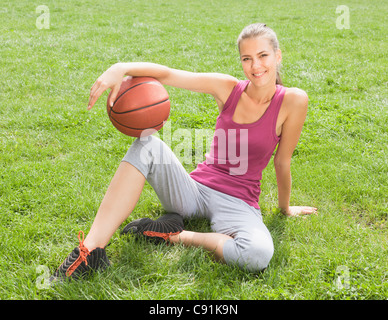 Woman holding basketball on grass - Stock Photo