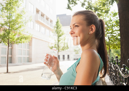 Woman drinking water on park bench - Stock Photo