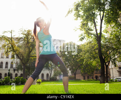 Woman stretching in urban park - Stock Photo