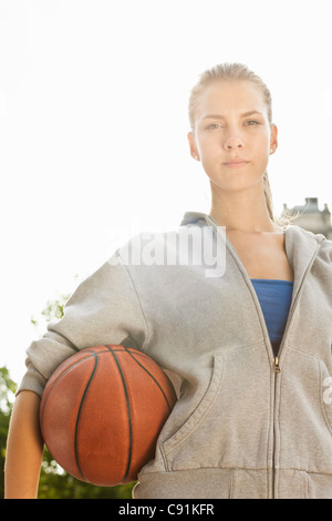 Woman carrying basketball outdoors - Stock Photo