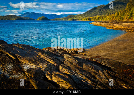 Sunlit rocks line the blue waters of Settler's Cove,  Settler's Cove State Recreation Site, Ketchikan, Southeast - Stock Photo