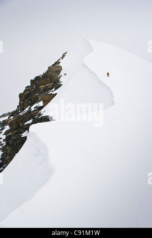 Skier ascends the north ridge of Mount Chamberlin in the Brooks Range, ANWR, Summer in Arctic Alaska - Stock Photo