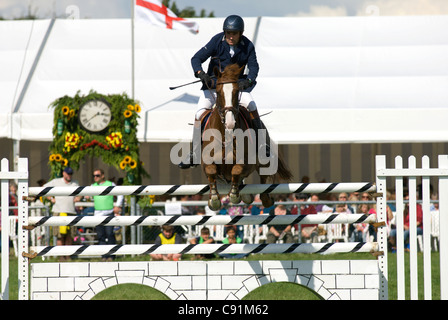 A competitor jumping a fence in the show jumping competition at the Edenbridge and Oxted Agricultural Show - Stock Photo