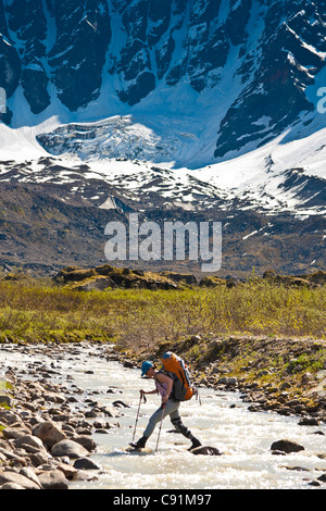 Female backpacker crossing the Babel River below South Buttress on the western flanks of the Revelation Mountains, - Stock Photo