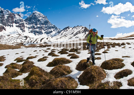 Female backpacker crossing snow and tundra tussocks above Babel River, Revelation Mountains, Alaska - Stock Photo