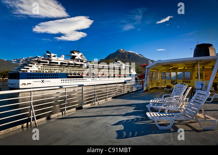 Alaska Marine Highway ferry moored next to a Celebrity Cruises cruise ship at the port of Skagway, Southeast Alaska, - Stock Photo
