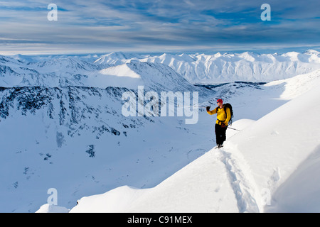 Skier climbs high to ski the steep southwest face of Kickstep Mountain, Turnagain Pass, Kenai Mountains in Southcentral - Stock Photo