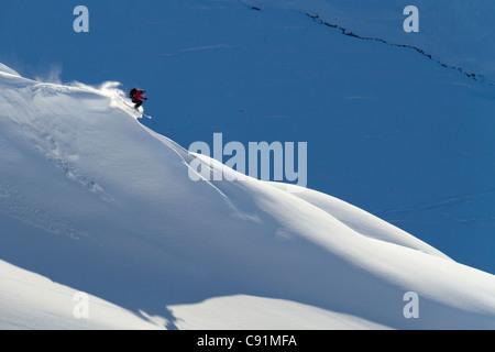 Man backcountry skiing powder snow on the south face of Eddies Ridge, Turnagain Pass, Kenai Mountains in Southcentral - Stock Photo